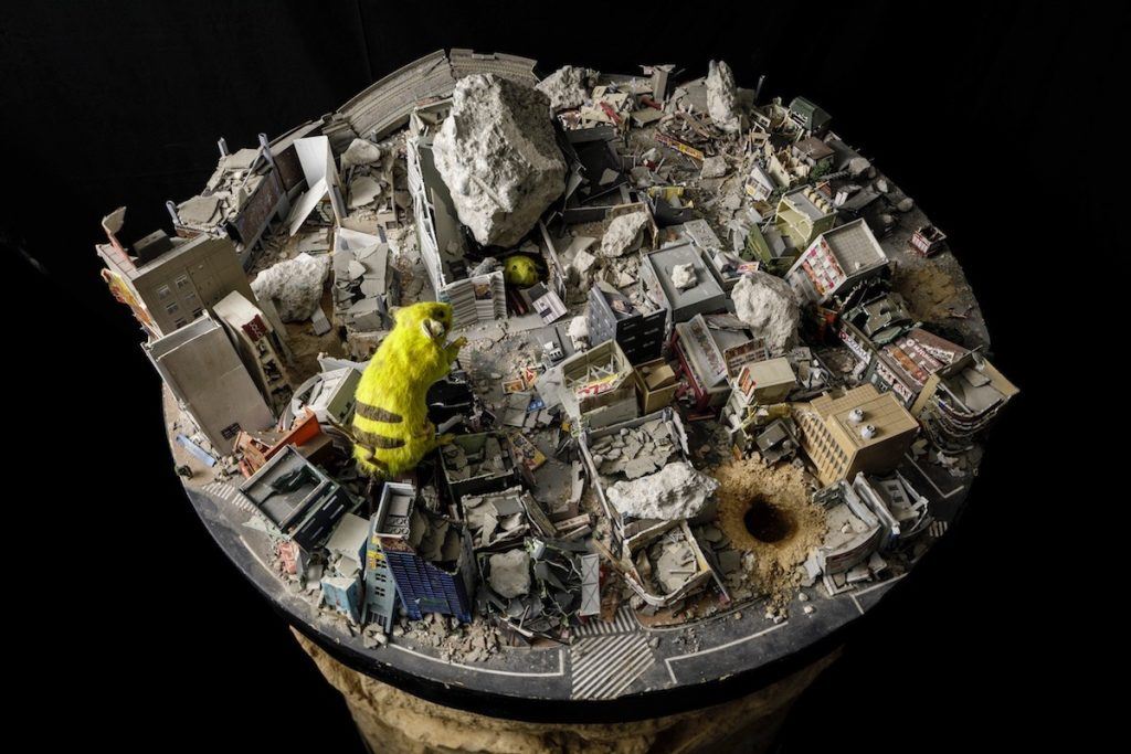 """SUPER RAT -Scrap & Build- 2017- Rats, stuffed rats captured in Shinjuku, demolished of Kabukicho diorama, soil, plaster, cat bones excavated in Kitakore Building, PVC sheet, iron frame, rat food, water, concrete fragments, video  This is the second version of the Kabukicho diorama and Super Rat, presented at """"So see you again tomorrow, too?"""" that were destroyed along with the demolition of Kabukicho Shopping District Promotion Association Building. Chim↑Pom dug a hole in the diorama of the completely destroyed cityscape and created a soil pedestal. By keeping rats that nest inside, the pedestal forms a street and city made by rats. After the exhibition, they will pour molten aluminum or plaster into the nest and create a three-dimensional work molding the cityscape as a pedestal, and combine it with the diorama and stuffed rats to complete the piece. Production support: Kenta Nishimura, Toshihiko Yo, Photo: Kenji Morita"""
