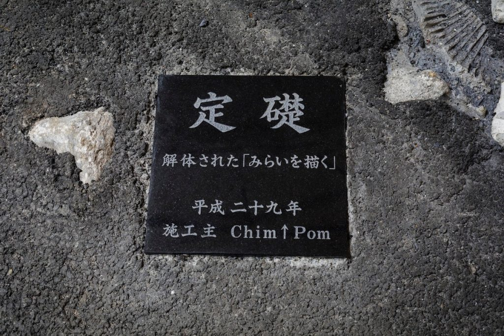 """Mirai's Reclaimed Land, 2017, After digging a hole inside Kitakore Building, Chim↑Pom buried Drawing Mirai, a blueprint drawing depicting sex worker Mirai's silhouette that was originally created for """"So see you again tomorrow, too?"""" With the motif of a young person who calls herself """"Mirai"""" (meaning """"future"""" in Japanese) and the rapid degradation of cyanotype as a material, they incorporated elements of burials, time capsules, and aging into their process. Furthermore, this spot was determined as the foundation of the Kitakore Building's renovation, and a teisoseki [foundation stone] was buried into the asphalt as a token. Since 2016, this piece has been transformed from Drawing Mirai → destroying the drawn Mirai → burying the destroyed Mirai – it will reach its final form when it is excavated during the demolition of Kitakore Building in the future."""