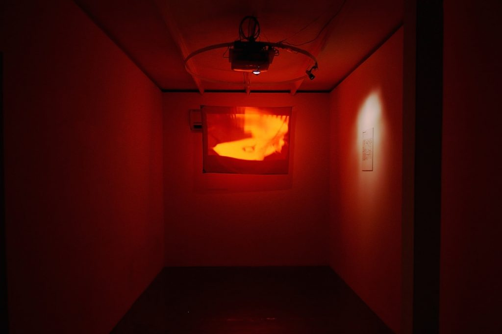 Enduring the Unendurable REAL TIMES, 2015, Even though we received a request from the curator to exhibit REAL TIMES at the Shanghai Biennale in 2012, Chim↑Pom was required to change the exhibiting work at the very last minute. The reason was due to the Senkaku islands dispute, which was intensifying at the time. The problem with the work was the appearance of the Rising Sun flag that one of the members then transformed into a nuclear mark with spray paint, made near the nuclear power plant in Fukushima. This was a rare complaint as this work is often seen to criticize Japan. Massive street demonstrations were happening in Shanghai just before the biennale, and the number of Japanese tourists dropped significantly. Certainly it was a dangerous time. By the way, this work was made into a version to be projected on a red flag in order to neutralize the red circle in the center of the Japanese flag. 2012年の上海ビエンナーレの際、キュレーターから《REAL TIMES》の展示をリクエストされたが、直前になって展示作品の変更を要請される。当時激化していた尖閣諸島問題が原因だった。メンバーが原発の近くで旗に改変していくマークをスプレーで描くのだが、いちど日の丸になっているのが問題とのこと。日本Disと受け取られがちな本作にしてはめずらしいタイプのクレームだった。ビエンナーレ直前にも上海で大規模な反日デモが起き、日本人観光客も激減していたときだった。つまり、確かに危ない時期ではあった。ちなみに本作品は、赤い旗にプロジェクションをして、日の丸の赤を相殺するバージョンである。